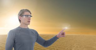 Businessman touching air in goggles in front of desert planet sun. Digital composite of Businessman touching air in goggles in front of desert planet sun royalty free stock photos