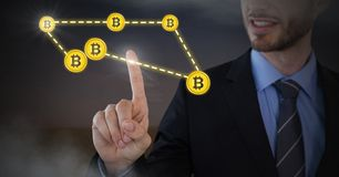 Businessman touching bitcoin graphic icons connecting. Digital composite of Businessman touching bitcoin graphic icons connecting Royalty Free Stock Photos