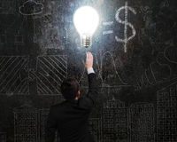 Businessman touching brightly light bulb illuminated dark doodle Stock Photography