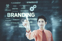 Businessman touching a button of branding. Image of young businessman touching a button of branding on the virtual screen royalty free stock photo