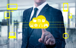 Businessman touching a cloud connected to many objects on a virtual screen, concept about internet of things Royalty Free Stock Images