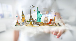 Businessman touching a cloud full of famous monuments with his f. Businessman on blurred background touching a cloud full of famous monuments with his finger 3D Stock Photo