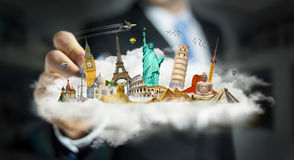 Businessman touching a cloud full of famous monuments with his f. Businessman on blurred background touching a cloud full of famous monuments with his finger 3D Royalty Free Stock Image