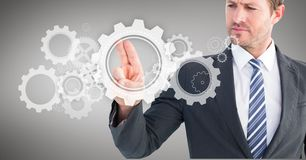 Businessman touching cog wheel on digital screen against grey background Stock Photo