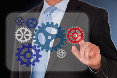 Businessman touching cogs. Body of businessman touching cogwheels on touchscreen Stock Photos