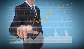 Businessman touching a curve of a chart Stock Images