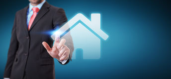 Businessman touching 3D rendering icon house with his finger. Businessman on blurred background touching 3D rendering icon house with his finger Royalty Free Stock Photos