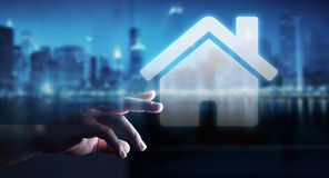 Businessman touching 3D rendering icon house with his finger. Businessman on blurred background touching 3D rendering icon house with his finger Stock Photo