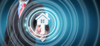 Businessman touching 3D rendering icon house with his finger. Businessman on blurred background touching 3D rendering icon house with his finger Stock Images