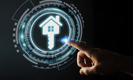 Businessman touching 3D rendering icon house with his finger. Businessman on blurred background touching 3D rendering icon house with his finger Royalty Free Stock Photography