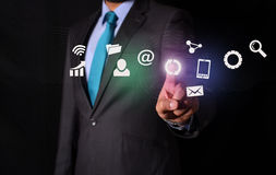 Businessman touching digital icons screen on black background.  Stock Images