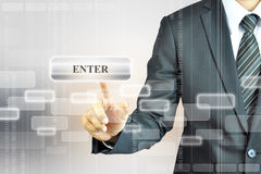 Businessman touching ENTER button on virtual screen Stock Photo