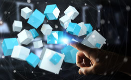 Businessman touching flying blue shiny cube 3D rendering. Businessman on blurred background touching flying blue shiny cube 3D rendering Royalty Free Stock Image