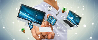 Businessman touching flying desk laptop phone and tablet with hi. Businessman on blurred background touching flying desk laptop phone and tablet with his finger Stock Image