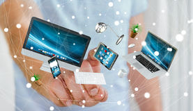 Businessman touching flying desk laptop phone and tablet with hi. Businessman on blurred background touching flying desk laptop phone and tablet with his finger Stock Photo