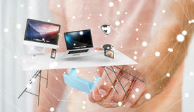 Businessman touching flying desk laptop phone and tablet with hi. Businessman on blurred background touching flying desk laptop phone and tablet with his finger Stock Images
