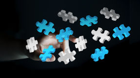 Businessman touching flying puzzle pieces 3D rendering Royalty Free Stock Images