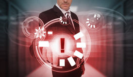 Businessman touching futuristic warning icon interface Royalty Free Stock Photos