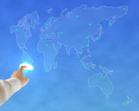 Businessman touching glowing cloud with worldwide map background. In blue sky Stock Images