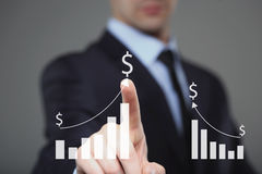 Businessman Touching a Graph Indicating Growth. dollar sign Royalty Free Stock Images