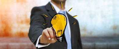 Businessman touching hand drawn lightbulb Royalty Free Stock Images