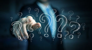 Businessman touching hand drawn question marks with his fingers Royalty Free Stock Photography