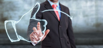 Businessman touching hand drawn thumb up sketch Royalty Free Stock Image