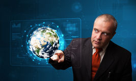 Businessman touching high-tech 3d earth panel Stock Photos