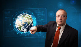 Businessman touching high-tech 3d earth panel. Businessman standing and touching high-tech 3d earth panel Royalty Free Stock Image