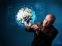 Businessman touching high-tech 3d earth panel. Businessman standing and touching high-tech 3d earth panel Royalty Free Stock Photos