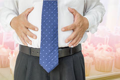 Businessman. Touching his stomach with cupcake photo background stock photo