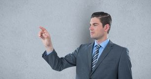 Businessman touching imaginary screen over gray background Stock Photo