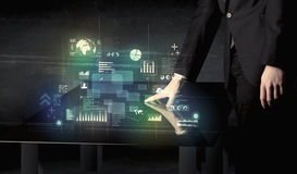 Businessman touching interactive modern desk with technology ico. Ns on table Stock Image