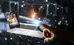 Businessman touching laptop phone and tablet with his finger 3D. Businessman on blurred background touching laptop phone and tablet with his finger 3D rendering Royalty Free Stock Images