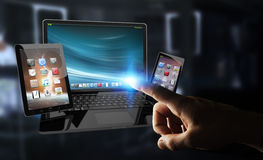 Businessman touching laptop phone and tablet with his finger 3D. Businessman on blurred background touching laptop phone and tablet with his finger 3D rendering Stock Photography