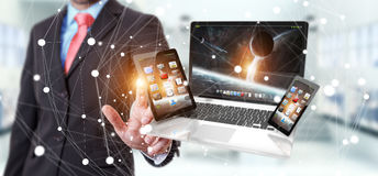 Businessman touching laptop phone and tablet with his finger 3D. Businessman on blurred background touching laptop phone and tablet with his finger 3D rendering Royalty Free Stock Image