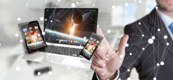 Businessman touching laptop phone and tablet with his finger 3D. Businessman on blurred background touching laptop phone and tablet with his finger 3D rendering Stock Photos