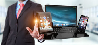 Businessman touching laptop phone and tablet with his finger 3D. Businessman on blurred background touching laptop phone and tablet with his finger 3D rendering Stock Photo