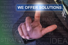 Businessman touching WE OFFER SOLUTIONS button on virtual screen royalty free stock image