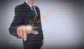 Businessman touching an orange curve Stock Photos