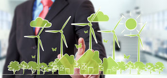 Businessman touching renewable energy sketch. Businessman on blurred background touching renewable energy sketch Stock Image
