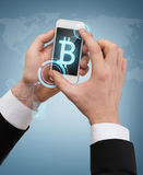 Businessman touching screen of smartphone. Business, internet and technology concept - businessman touching screen of smartphone with bitcoin sign on screen Royalty Free Stock Photography