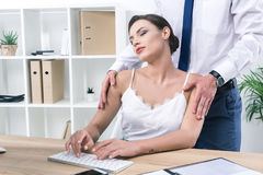 Businessman touching shoulders of his pretty colleague working with pc. At workplace Stock Image