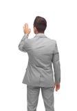 Businessman touching something imaginary Stock Photo