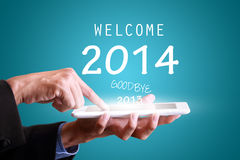 Businessman touching tablet pad for new year 2014 Royalty Free Stock Photos
