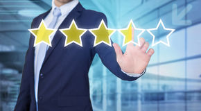 Businessman touching technology interface with ranking stars. View of a Businessman touching technology interface with ranking stars Stock Photo