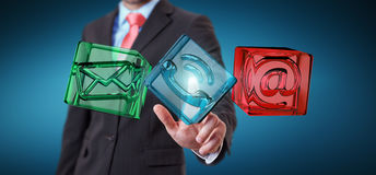 Businessman touching transparent cube contact icon with his fing. Businessman on blurred background touching transparent cube contact icon with his finger 3D Stock Photos