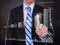 Businessman touching transparent screen with growing bar graph Royalty Free Stock Photos