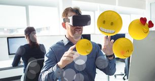 Businessman touching various emojis seen through VR glasses in office. Digital composite of Businessman touching various emojis seen through VR glasses in office Royalty Free Stock Photography