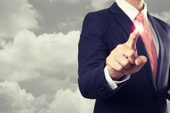 Businessman touching on virtual screen with cloud in sky background stock image